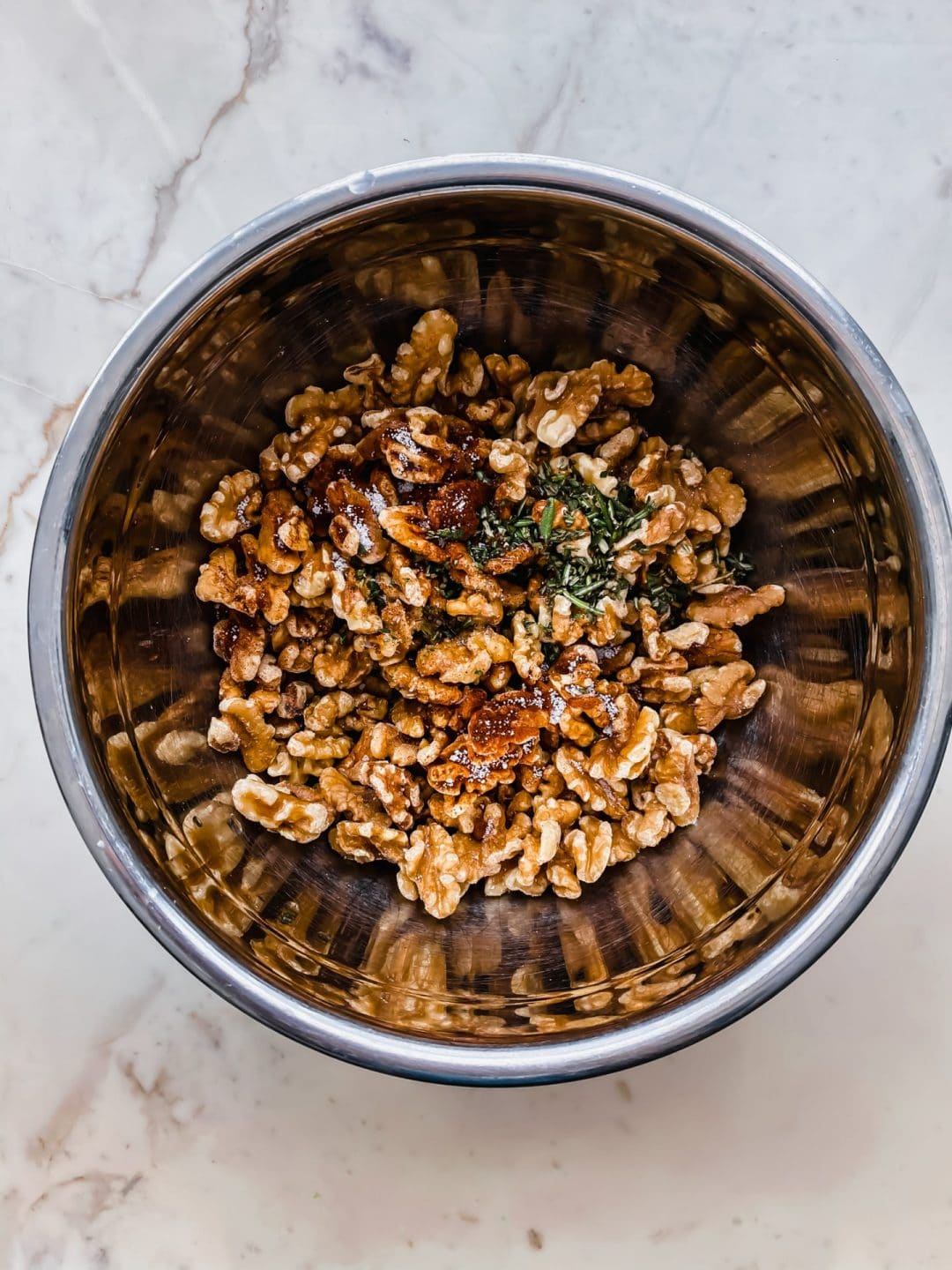A metal mixing bowl filled with the ingredients for Chipotle Rosemary Roasted Walnuts.