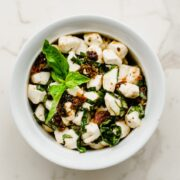 A white bowl filled with Italian marinated mozzarella pearls with a sprig of fresh basil on top.