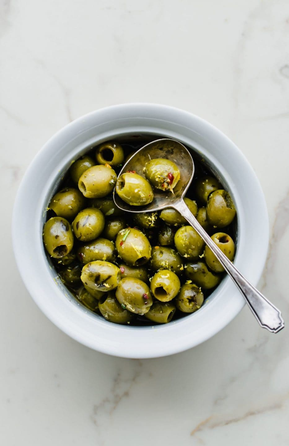 A white bowl filled with warm olives with lemon and rosemary with an antique spoon on the side.