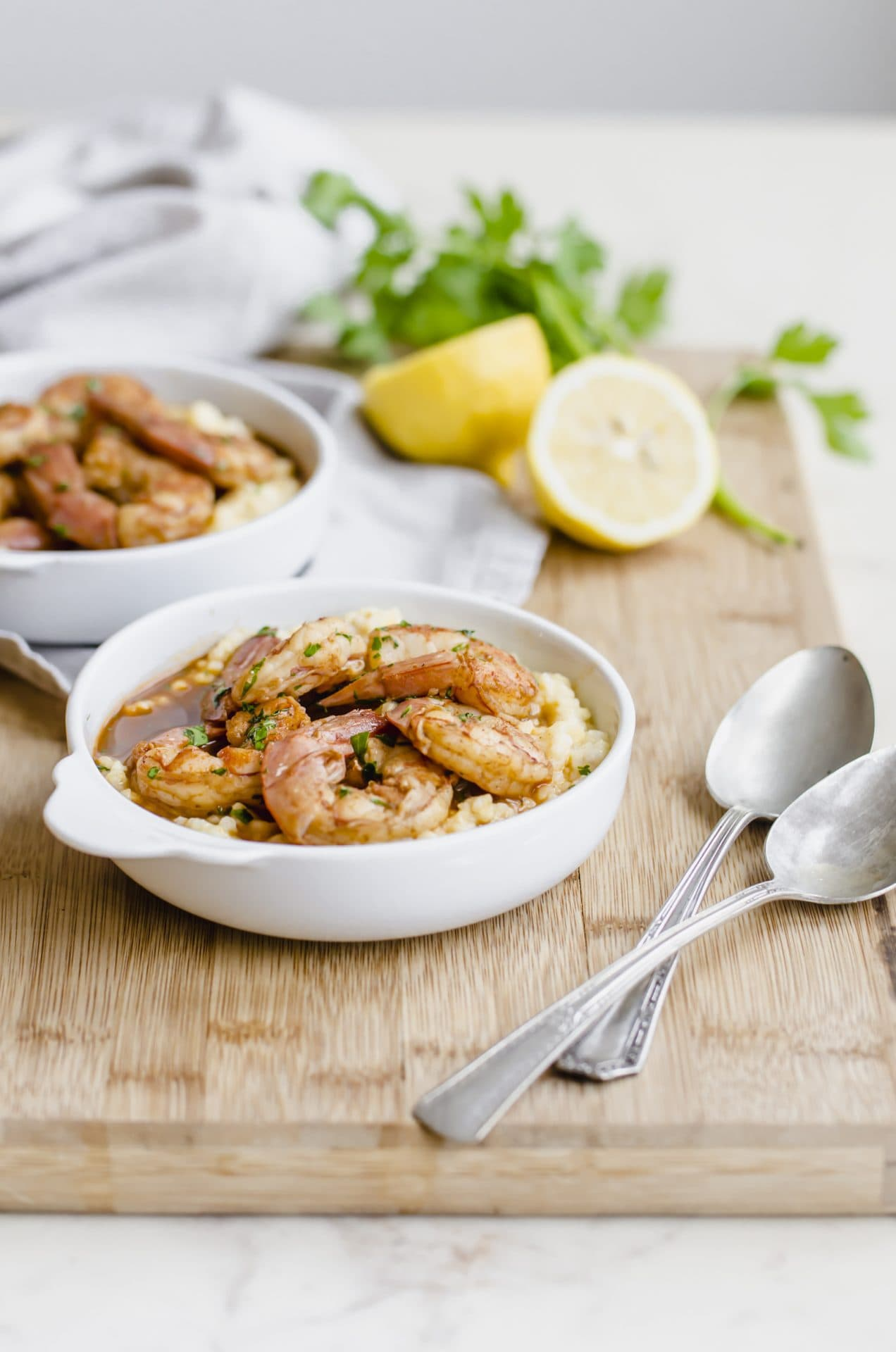 An overhead shot of two bowls of barbecue shrimp and grits on a cutting board with a lemon on the side.