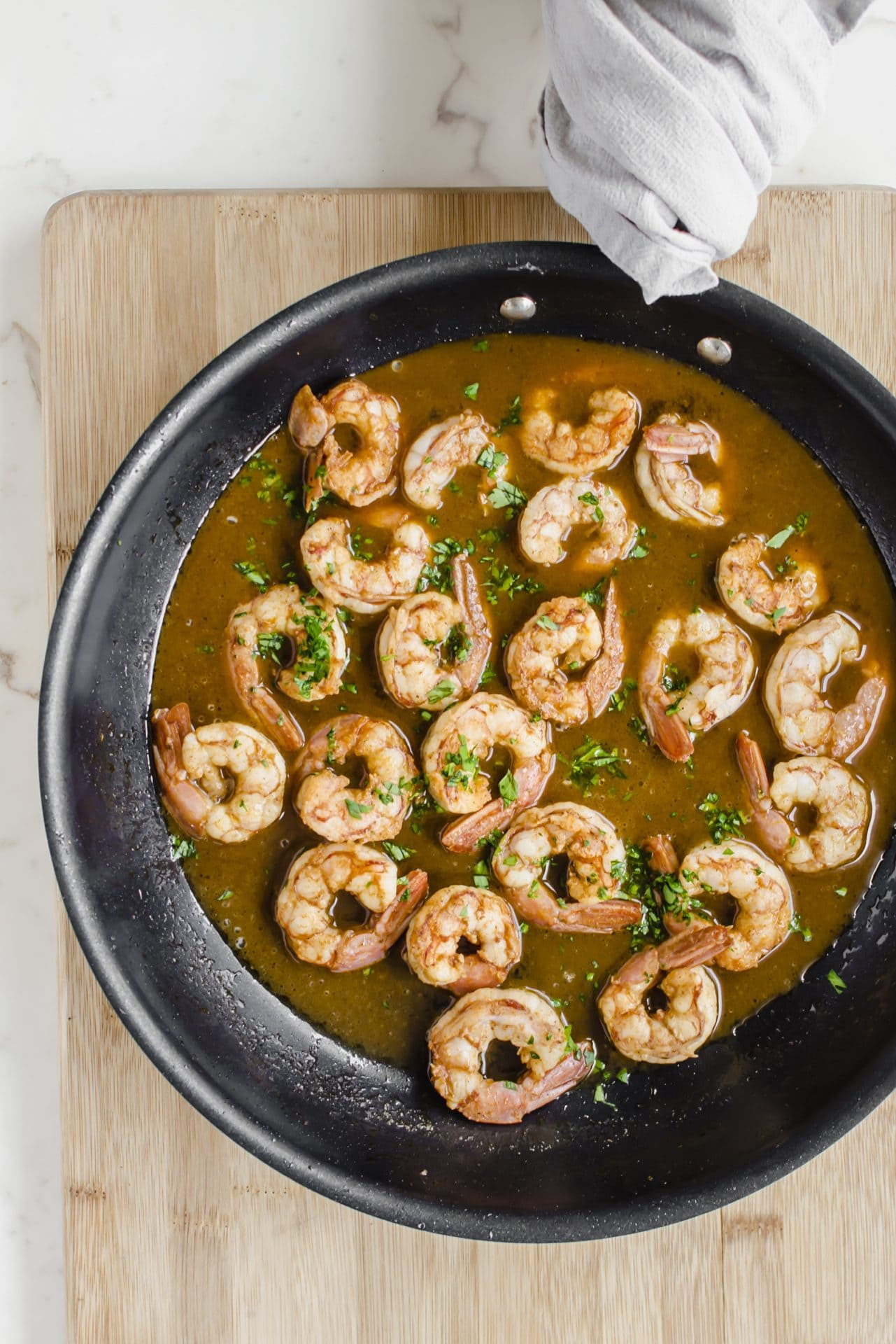 An overhead shot of a large skillet with shrimp and sauce inside of it.