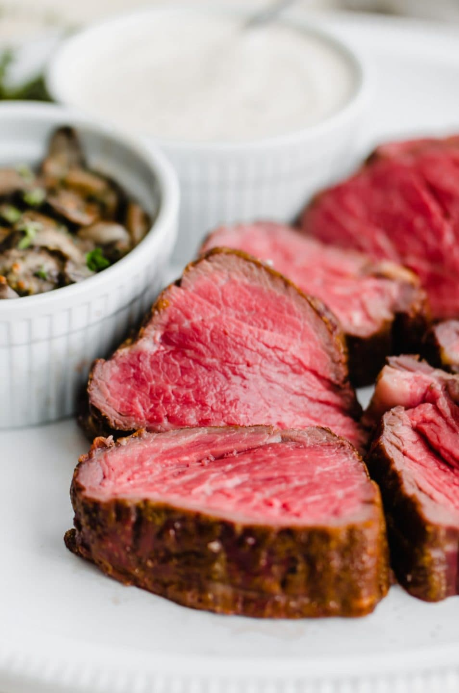 A close up shot of medium-rare beef tenderloin slices on a white platter.
