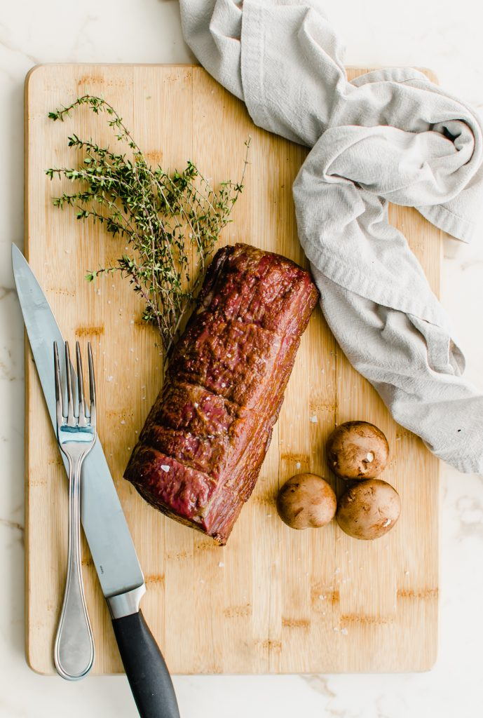A whole roasted beef tenderloin on a cutting board with a carving knife and fork on the side.