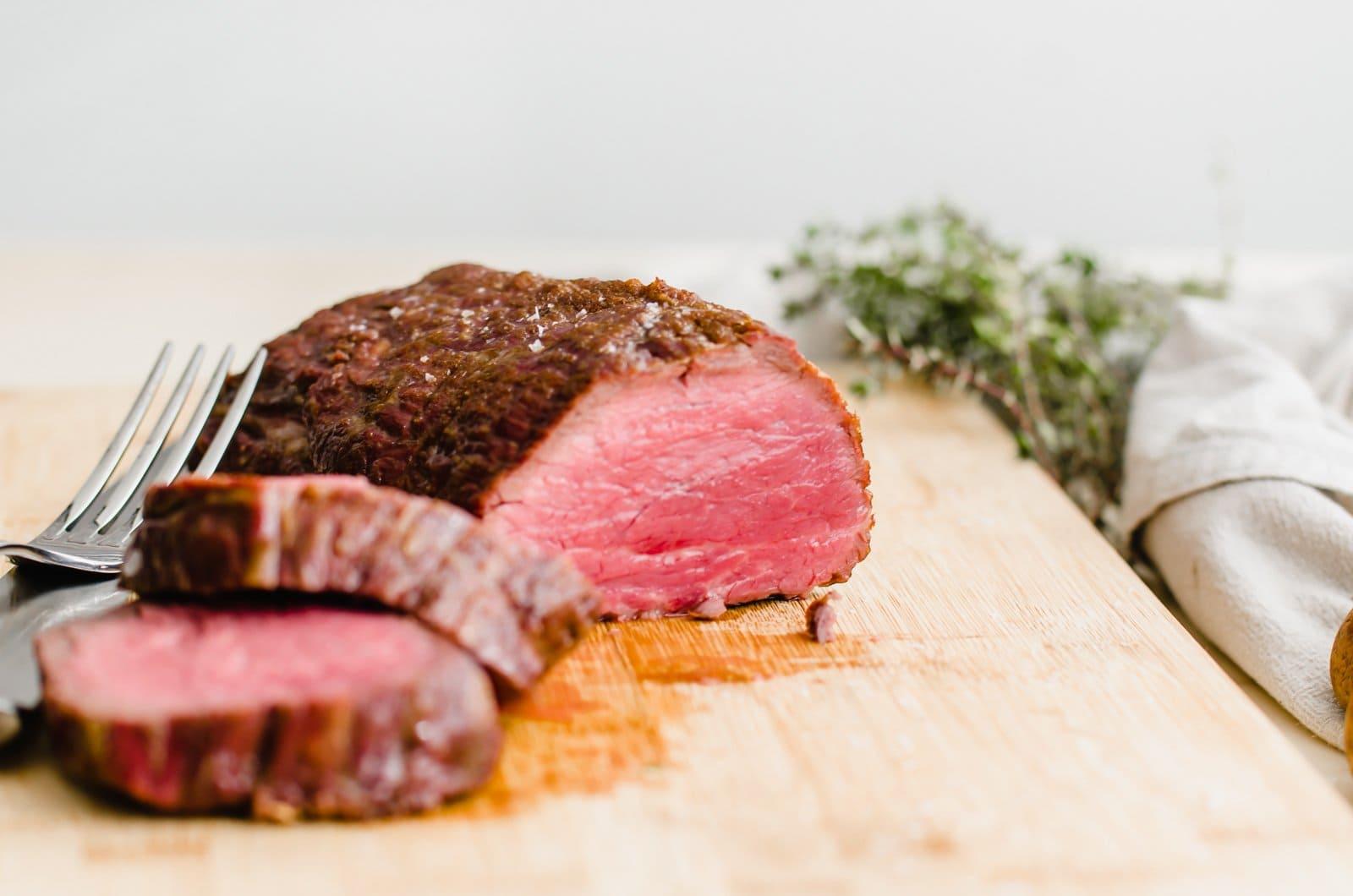 A close up shot of beef tenderloin being sliced.