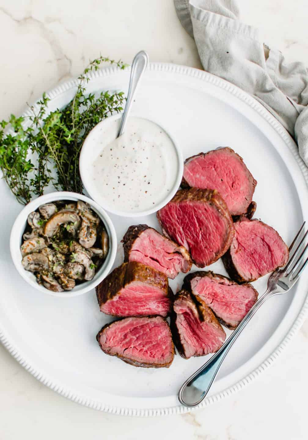 A white round platter with sliced beef tenderloin ad dishes of horseradish cream and marsala mushrooms.