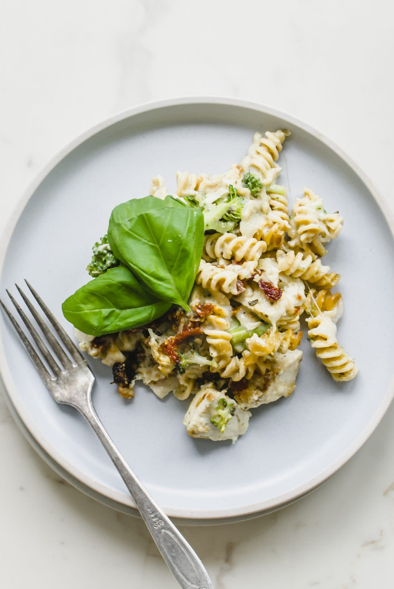 A blue plate with a serving of chicken rotini bake with a sprig of basil on top and a fork on the side.