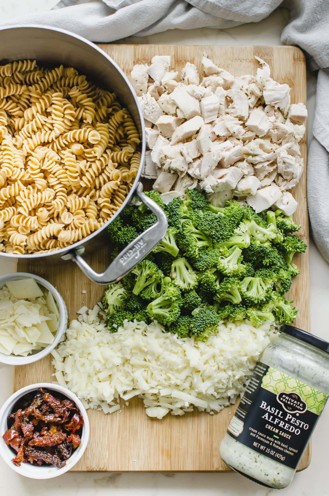A cutting board with all of the prepped ingredients spread out for making Chicken Rotini Bake.