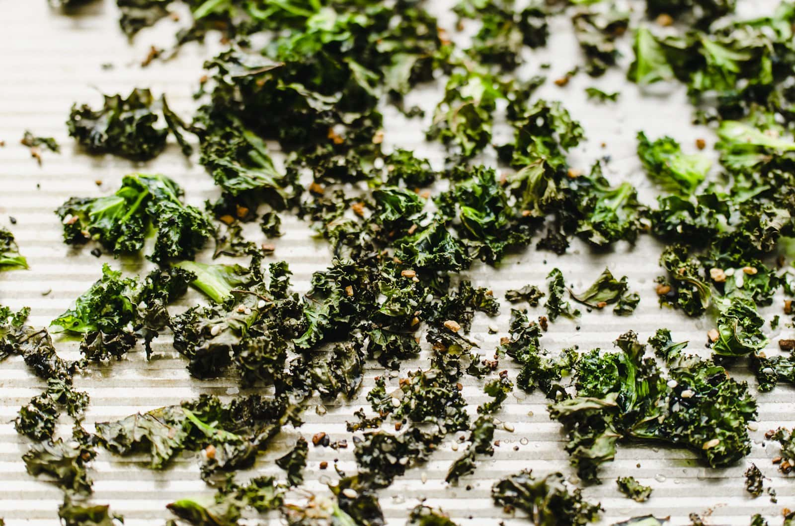 A close-up shot of baked kale chips on a baking sheet.