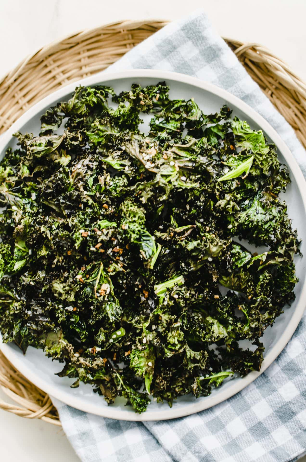 A blue plate of kale chips on a gingham dish towel.