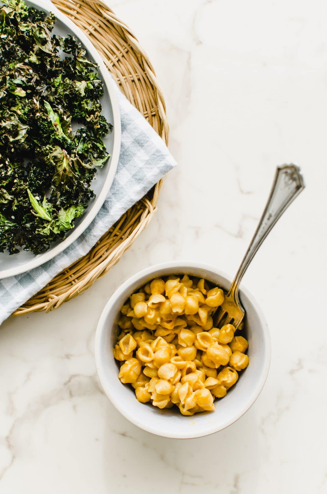 A bowl of mac and cheese with a plate of kale chips on the side.