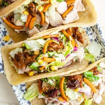 Rotisserie chicken tacos on a speckled blue tray on a white marble counter.