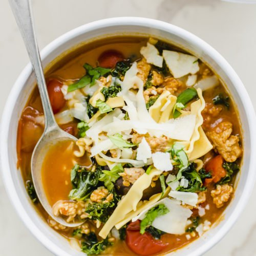 A white bowl filled with lasagna soup and topped with cheese and a spoon in the bowl.