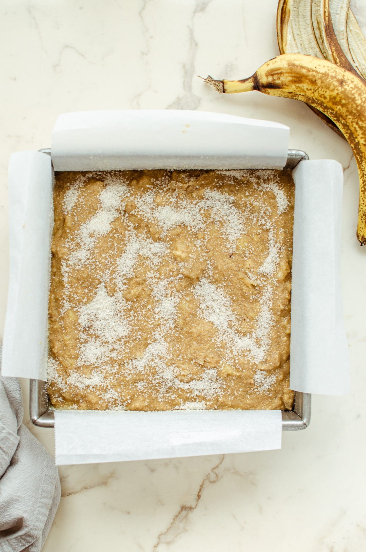Unbaked banana bread batter in a square cake pan sprinkled with sugar on top.