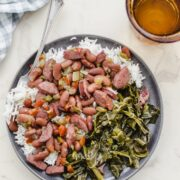 A gray plate of red beans and rice with a gingham dish towel and a glass of water on the side.