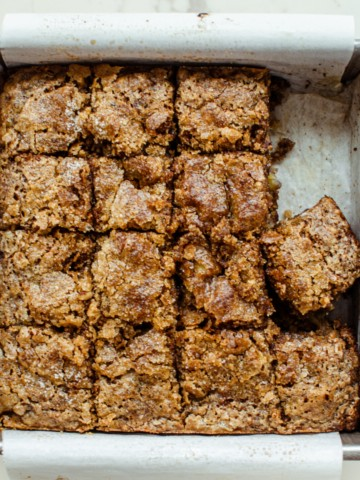 A square pan lined with parchment paper and filled with sliced squares of banana bread.