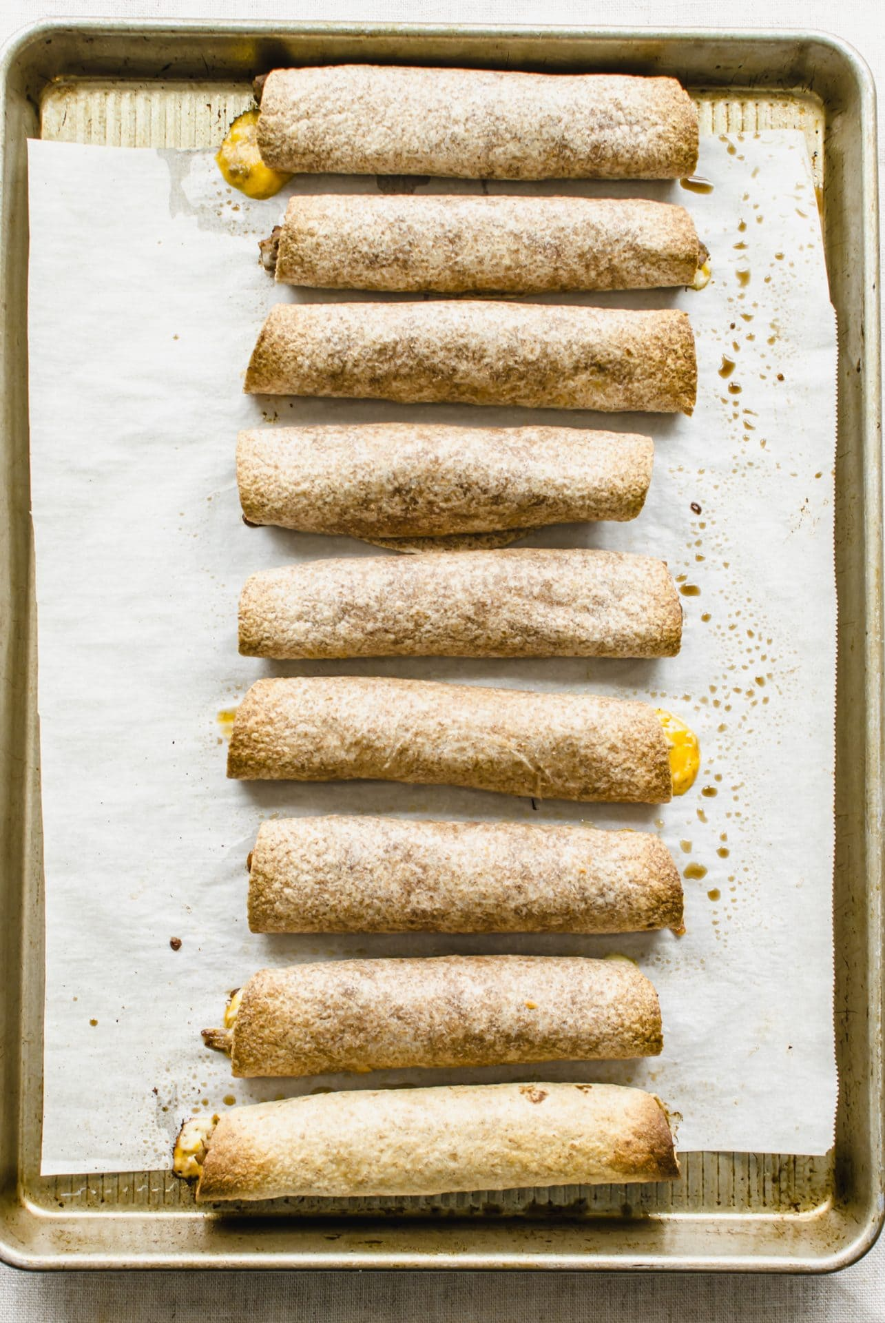 Baked beef taquitos on a sheet pan lined with parchment paper.