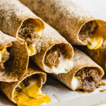 Stacked shredded beef taquitos on a sheet pan.