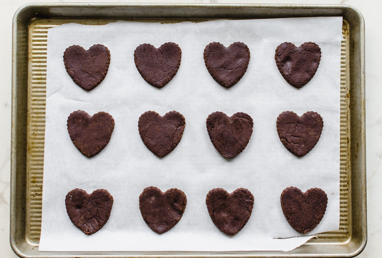 Unbaked heart-shaped chocolate cookies on a baking sheet with parchment paper.