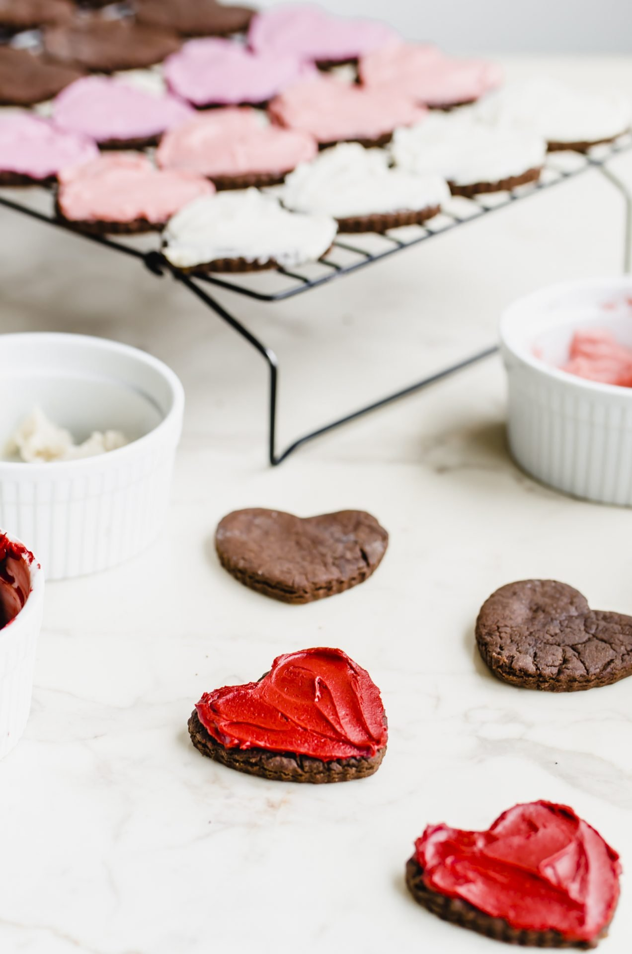 Frosted heart chocolate cutout cookies on a white countertop with bowls of frosting on the side.