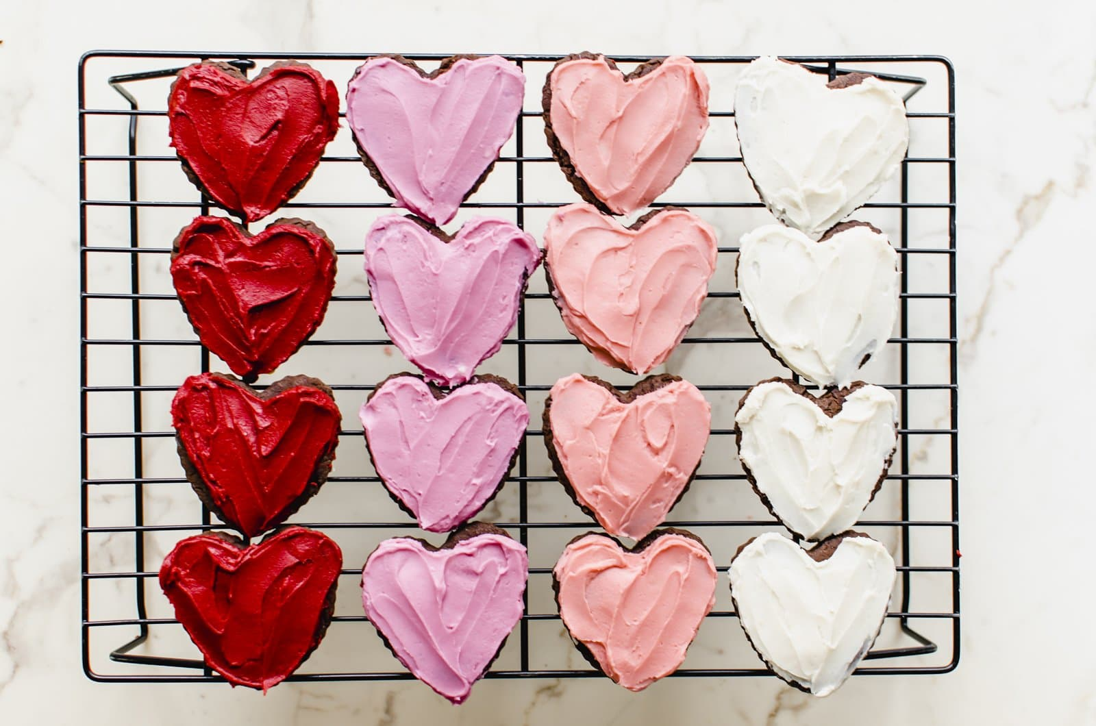 Rose of red, pink, peach and white frosted cutout cookies on a wire baking rack.