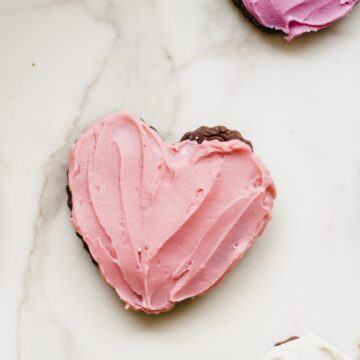 A frosted pink heart cookie on a white countertop.
