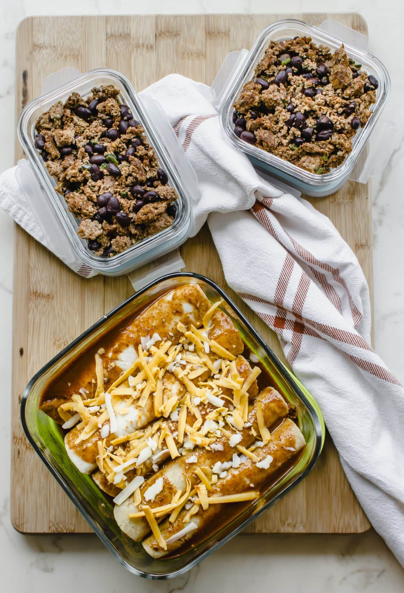 A freezer container filled with enchiladas and two meal prep containers with enchilada filling.
