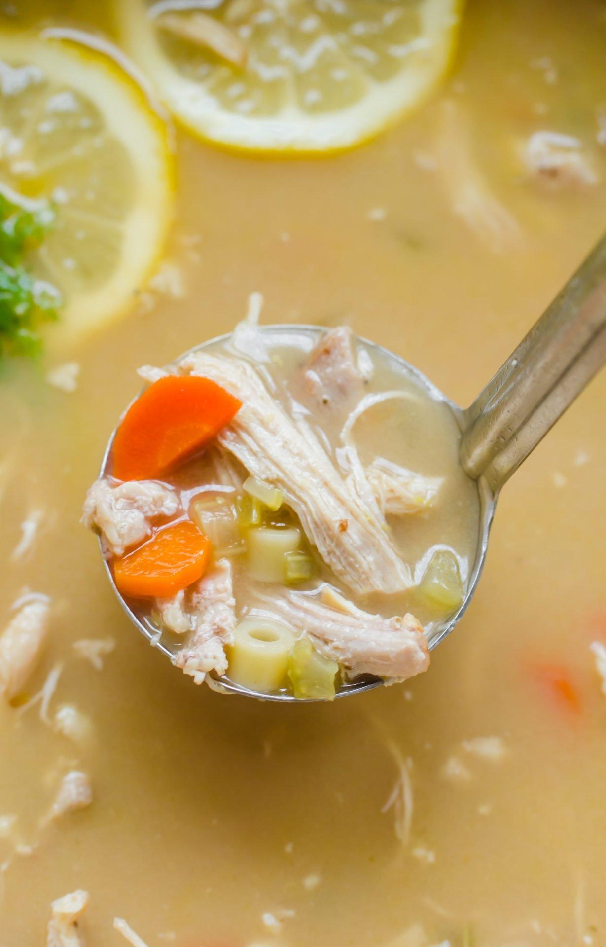 A ladle in a pot of lemon chicken noodle soup.