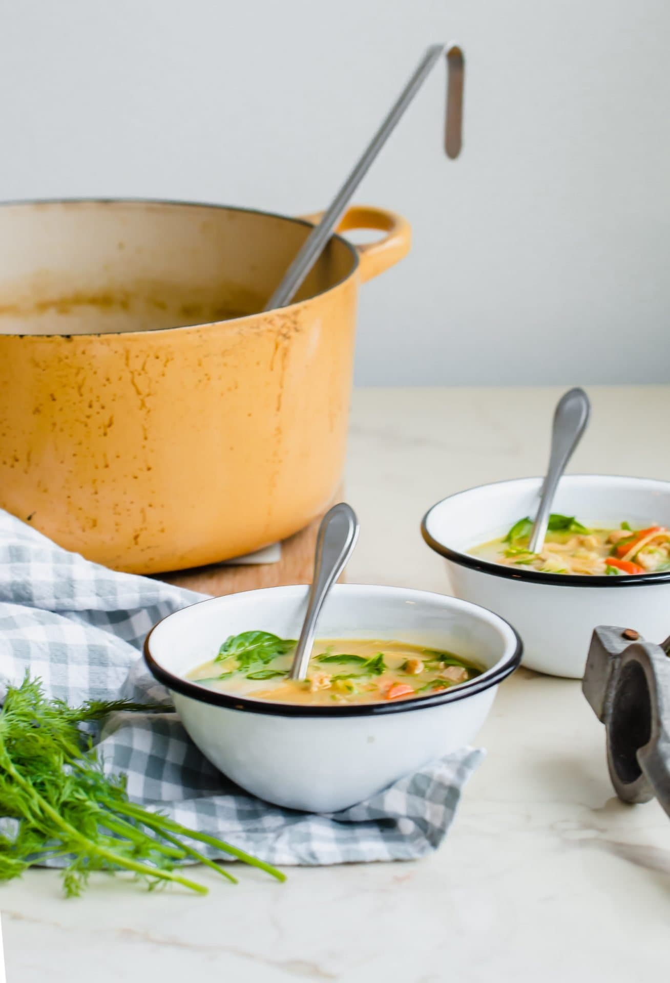 Two white enamel bowls filled with lemon chicken soup next to a pot of soup on the side.