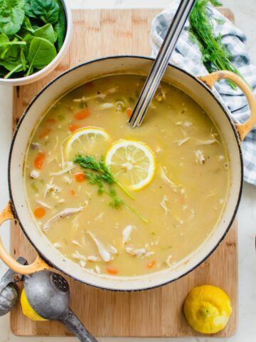 A yellow Dutch oven filled with lemony chicken and orzo soup with a ladle and lemons on the side.