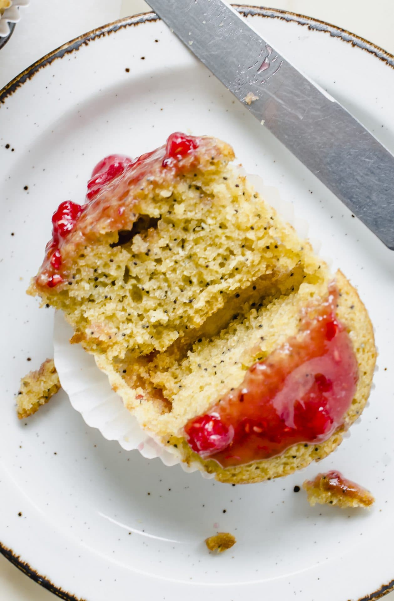 A lemon poppyseed muffins with fresh raspberry glaze on top cut down the center.