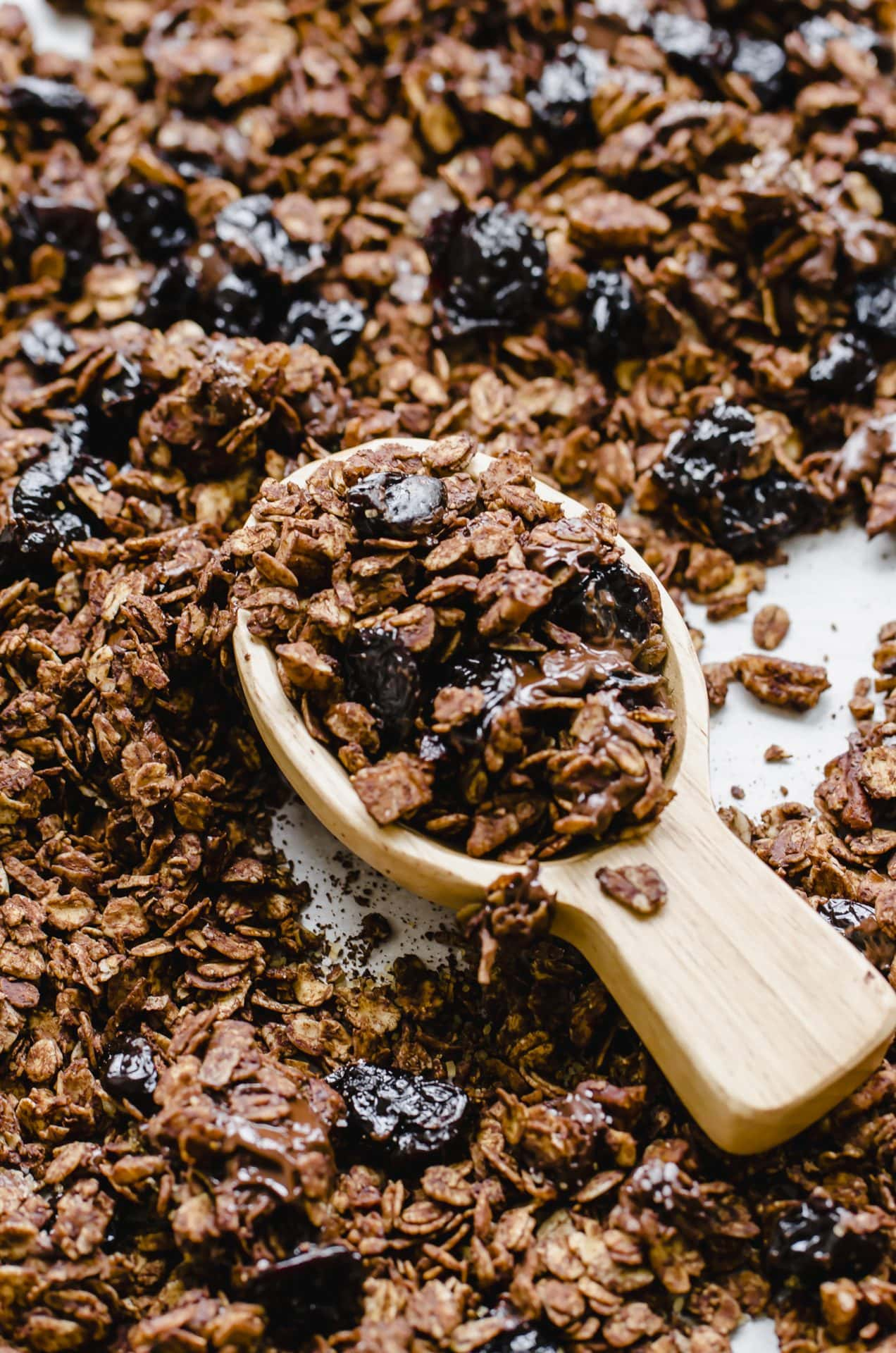 A wooden scoop filled with chocolate granola on a pan of granola.