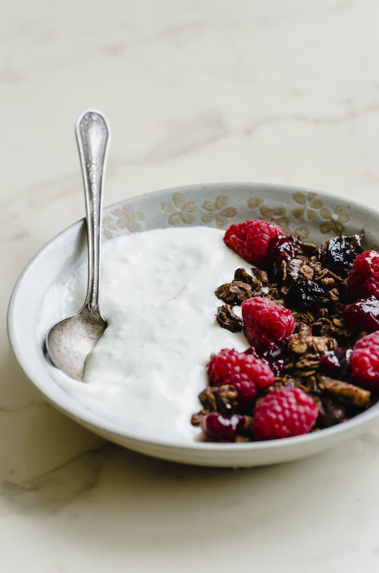 A gray stone bowl of yogurt topped with chocolate granola and raspberries with a spoon on the side.