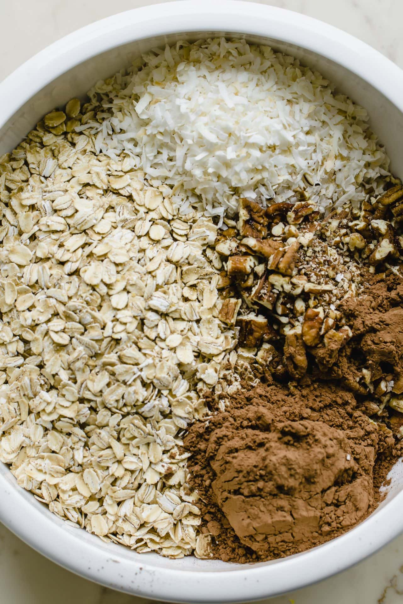 A white bowl with oats, coconut, pecans, and cocoa powder.