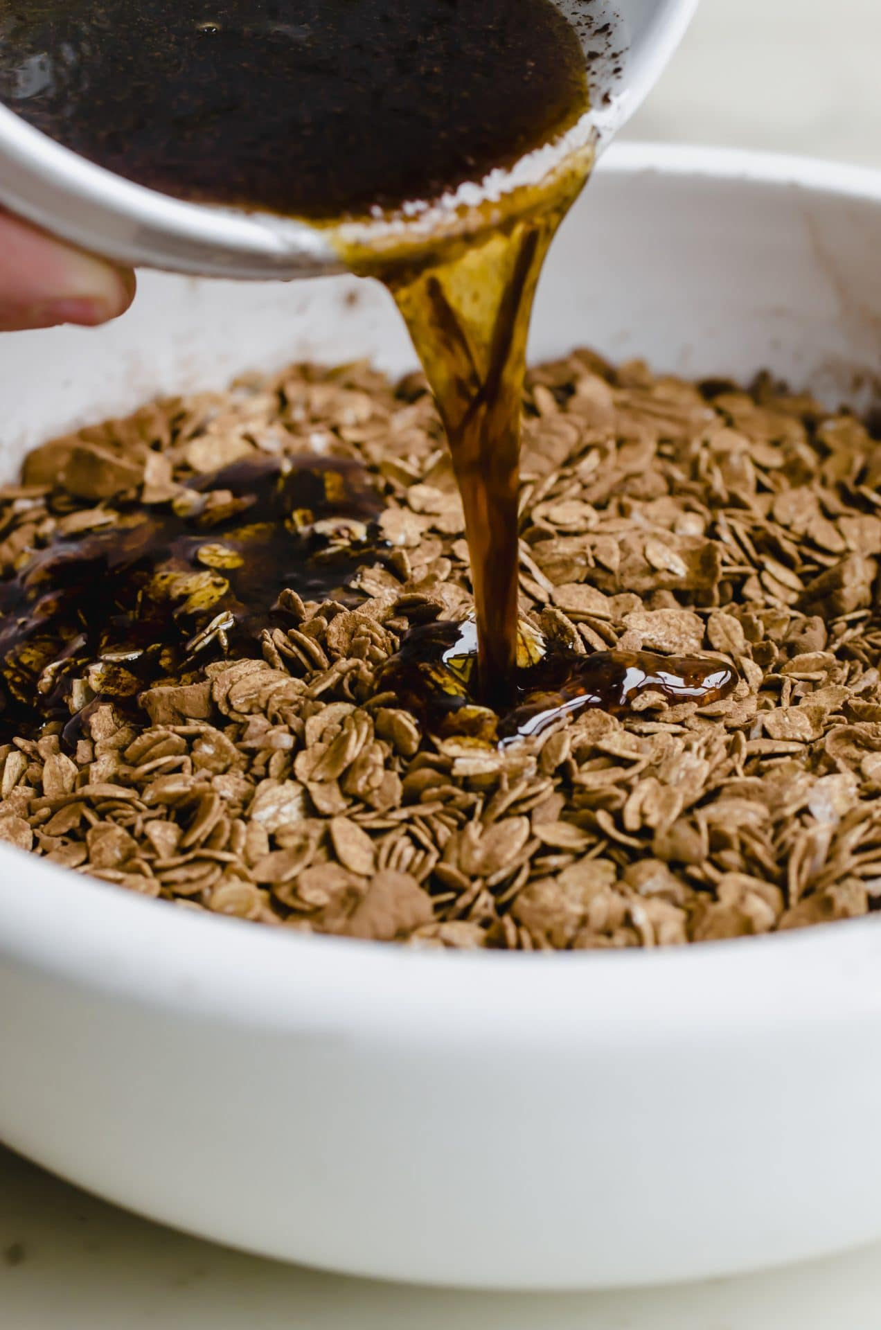 Maple syrup mixture pouring into an oat granola mixture in a white bowl.