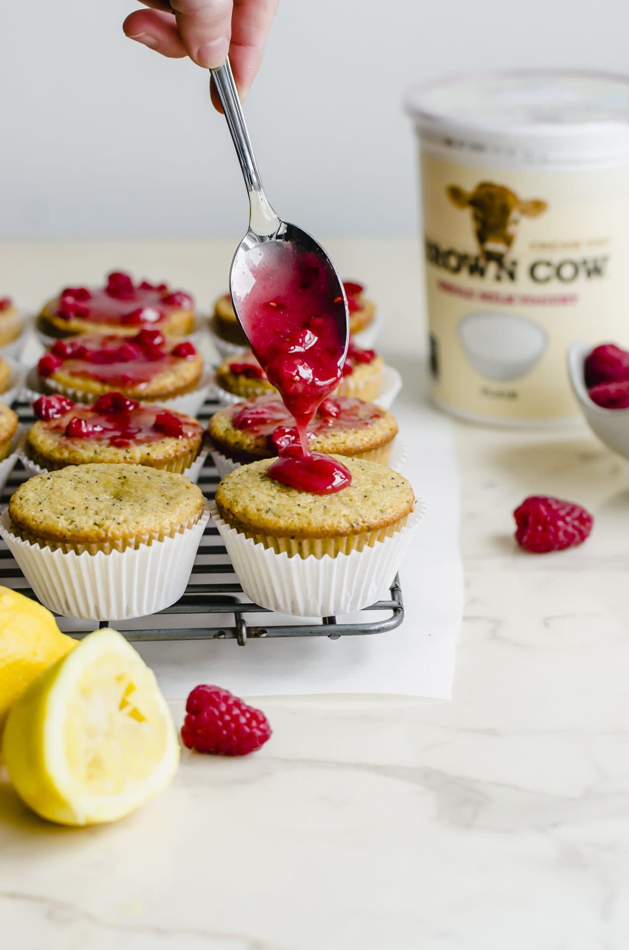 A spoon drizzling fresh raspberry glaze on a lemon poppyseed muffins.