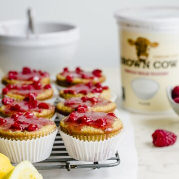 Glazed lemon poppyssed muffins on a wire rack with a container of yogurt in the background.