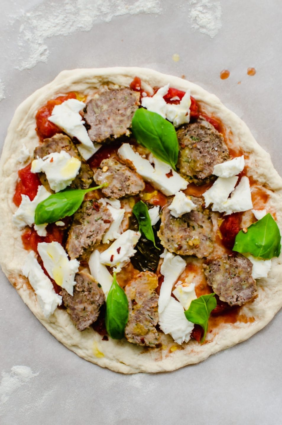 An unbaked meatball pizza on a sheet of parchment paper.