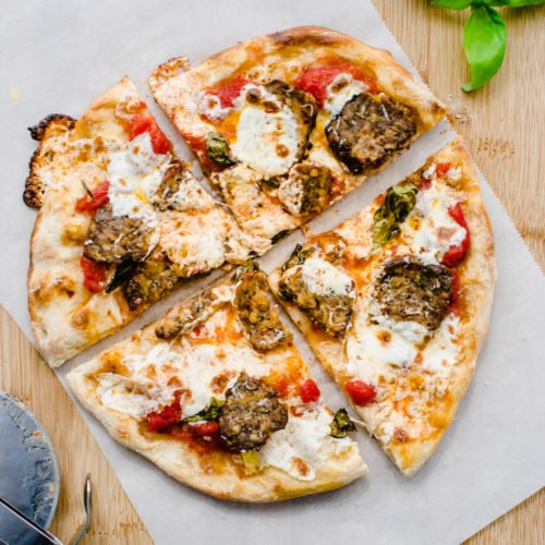 Overhead shot of a baked meatball pizza on a sheet of parchment paper.