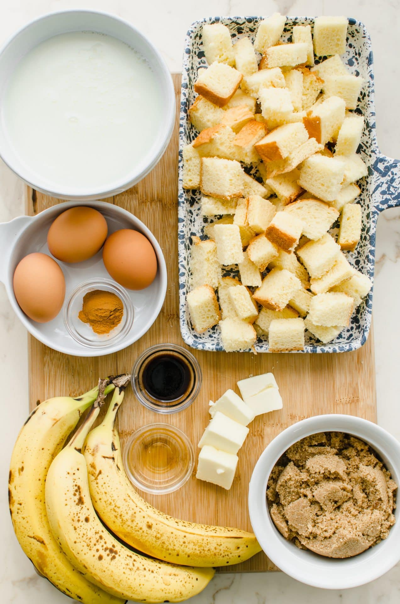 An overhead shot of ingredients in bowls on a wooden board for making bananas foster bread pudding.