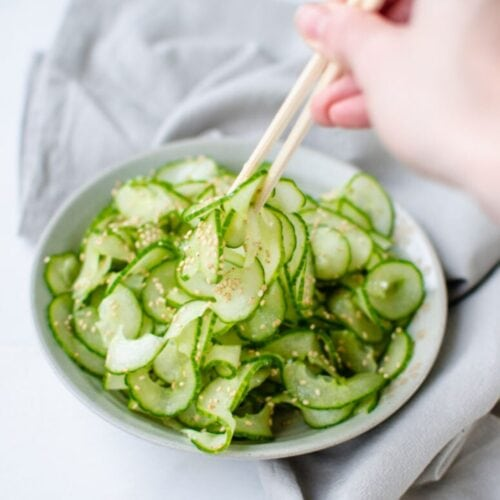 Spiralized cucumber sunomono salad with a hand shown using chopsticks to get a bite.