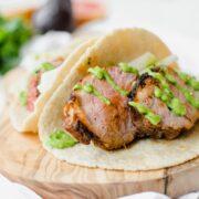 Photo of two pork tacos with avocado dressing.