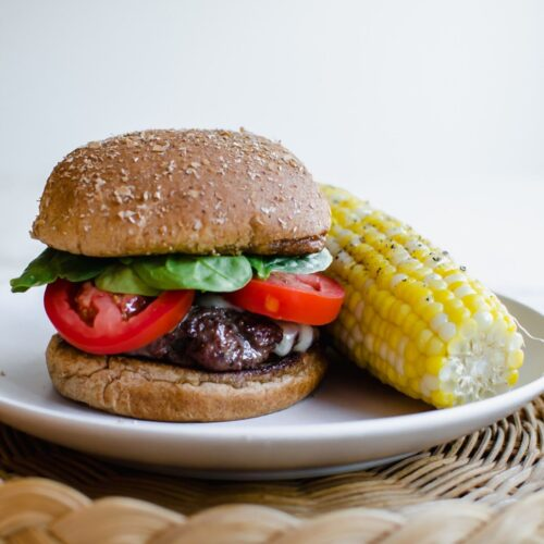 Hamburger on a plate with an ear of corn as a side.