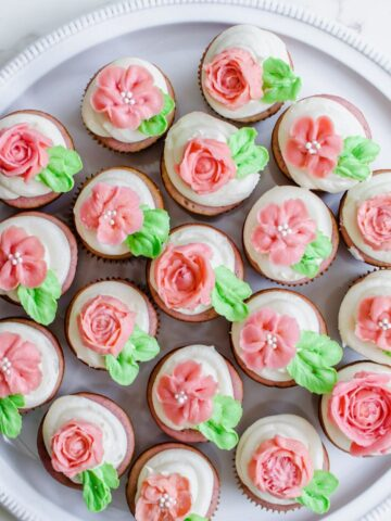 White serving tray with 19 strawberry cupcakes displayed. Each cupcake has an icing flower on top of it.