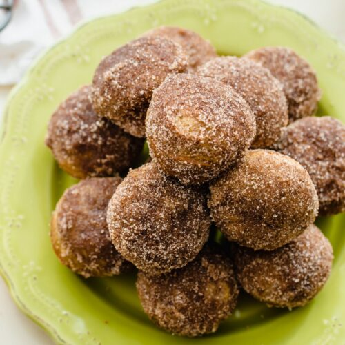 A green plate piled high with apple cinnamon donut holes.