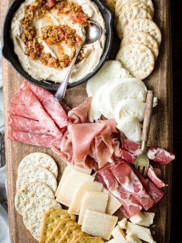 A wood serving tray with antipasto foods distributed over the top of it. Meats, cheeses, crackers, dips are included on the serving tray.