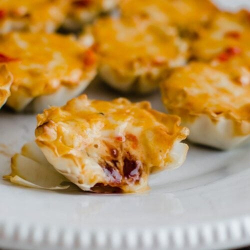 A close up of a plate of pimento cheese tartlets. The closest one has a bite out of it.