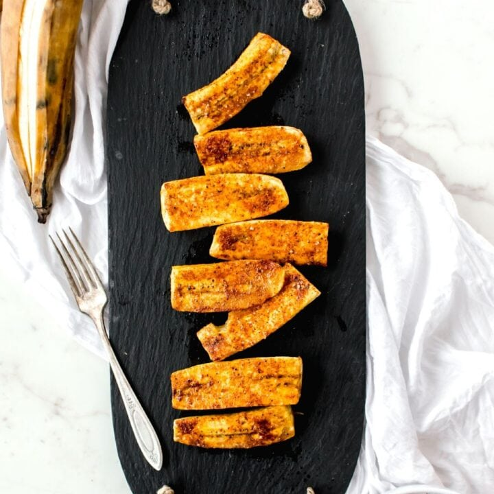 Overhead view of a slate tray with roasted plantains distributed over the top. Cinnamon is sprinkled on top of the plantains.