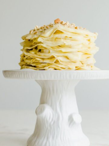 Side view of banana pudding crepe cake on a cake stand.