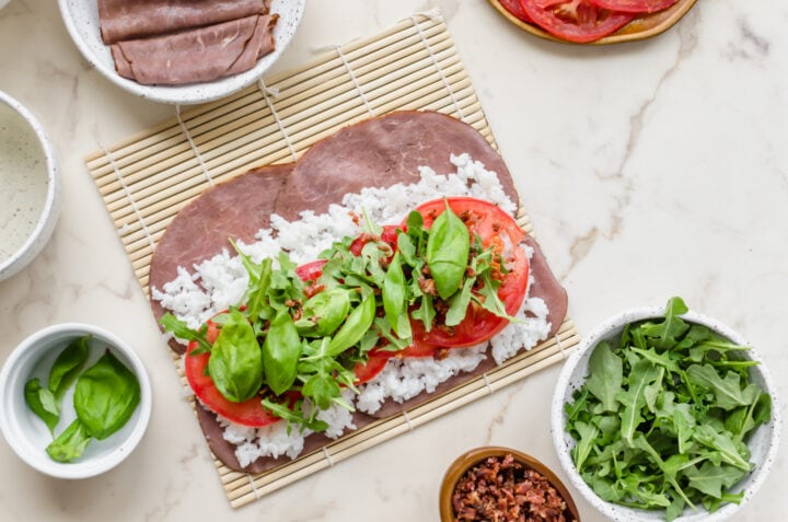 Ingredients piled on a bamboo mat for a BLT beefshi roll.