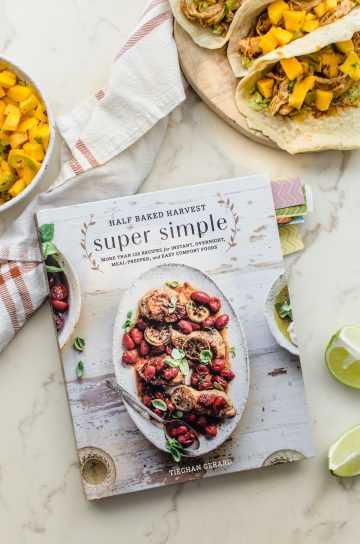 The Half Baked Harvest Super Simple cookbook on a white marble counter.
